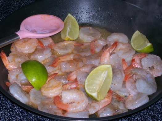 Shrimp, limes, and hot sauce in a skillet